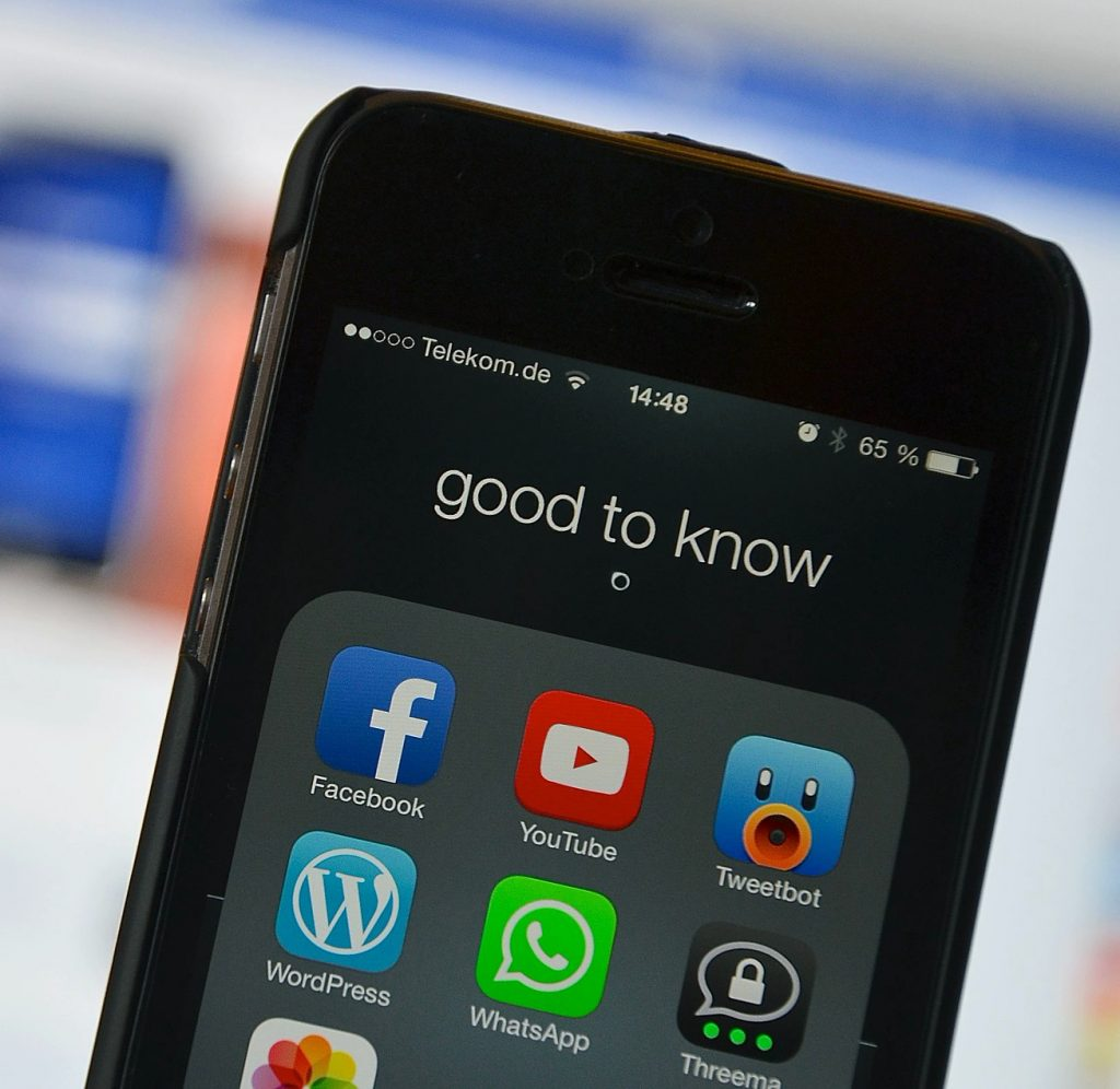 iPhone showing Facebook, YouTube and Twitter apps